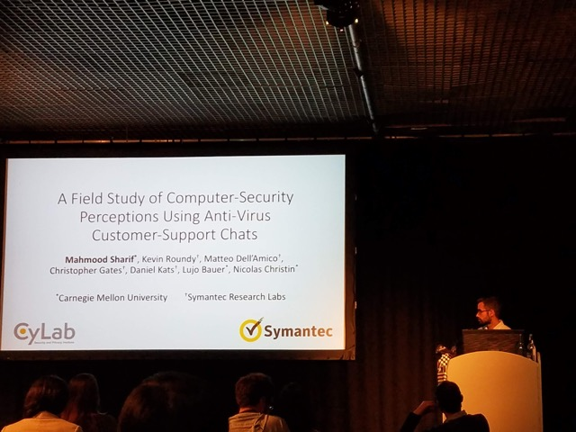 "A student standing at a podium next to a powerpoint slide with the title ""A Field Study of Computer-Security Perceptions Using Anti-Virus Customer-Support Chats."""